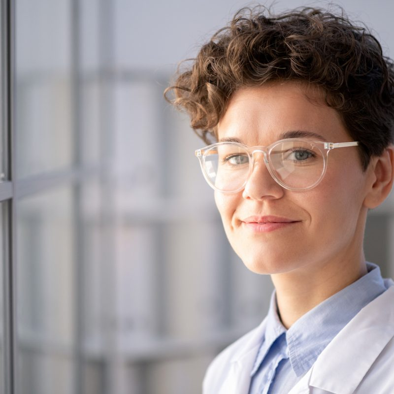 Portrait of smiling smart female medical worker in glasses standing in modern laboratory