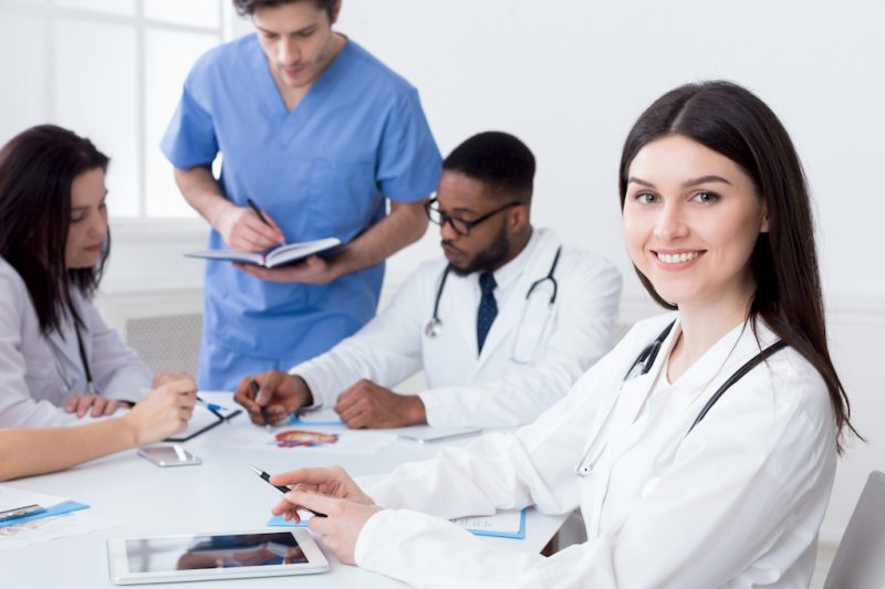Team of doctors having meeting in medical office, woman looking at camera