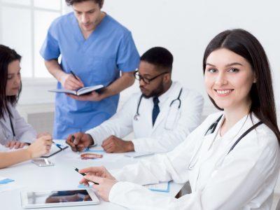Team of doctors having meeting in medical office, woman looking at camera
